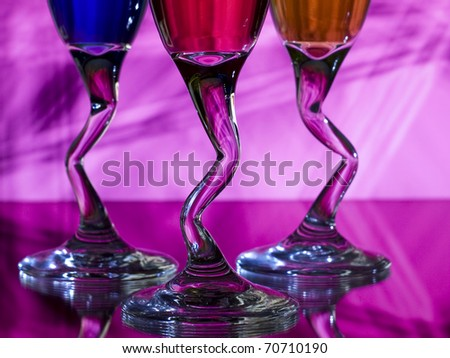 Curved stems of three glasses of liqueur on pink designed background - stock photo