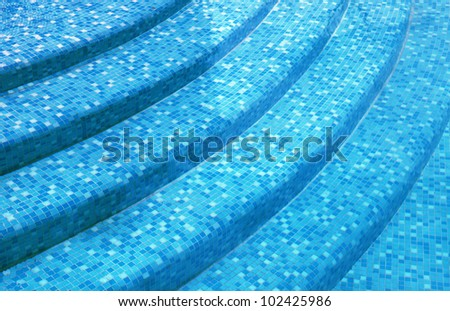 curved steps at the resort swimming pool with mixed blue tile mosaic - stock photo