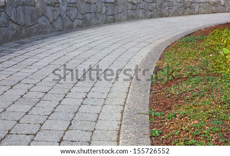 Curved stone path with stone wall - stock photo