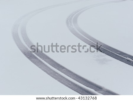 Curved tire tread marks in the snow