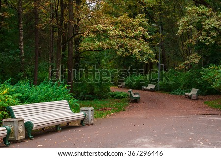 Curved walkway with empty benches in the autumn park