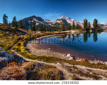 Curving mountain lake shore with perfect reflection, blue sky, and distant mountains - stock photo