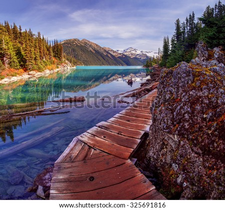 Curving path around a corner leading along a mountain creek towards distant snow capped mountains - stock photo