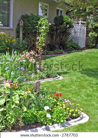 Curving perennial bed in a sunny side garden.