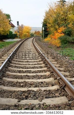 Curving train tracks, autumn foliage, Germany. - stock photo