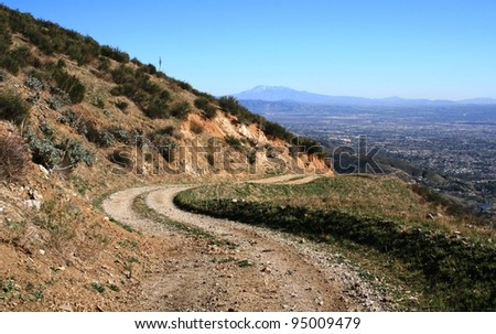 Curvy fire road down a mountain side, Southern California - stock photo