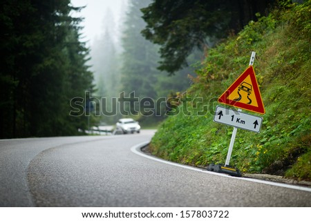 Curvy mountain road with slippery route sign and blurred white car in the background - stock photo