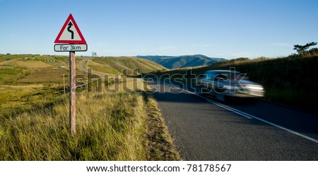 curvy road sign in rural country and speeding car - stock photo