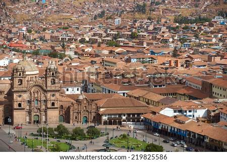 CUSCO, PERU - AUGUST 29, 2014: The historic Plaza de Armas in the historic former Inca capital of Cusco in Peru. The Iglesia de la Compania is the prominent red stone building facing the square. - stock photo