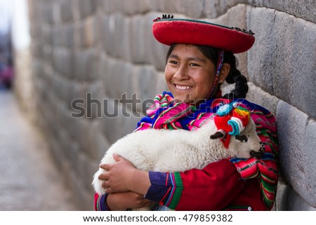 Cusco, Peru - May 14 : Jenni, a young woman dressed in colorful traditional native Peruvian closing holding a baby Lamb with Inca walls in the background. May 14 2016, Cusco Peru.