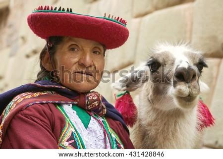 CUSCO, PERU-NOVEMBER 26 2011: Portrait of old peruvian quechua woman in traditional clothes with llama in Cusco - stock photo