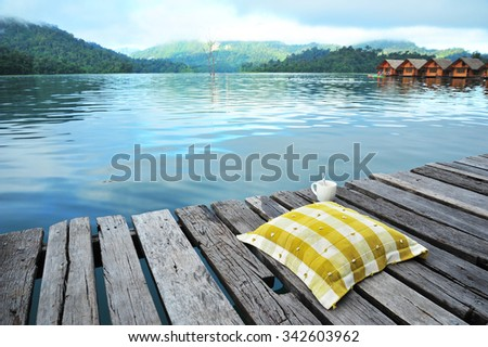Cushion and A Cup of Coffee Among the Lake - stock photo