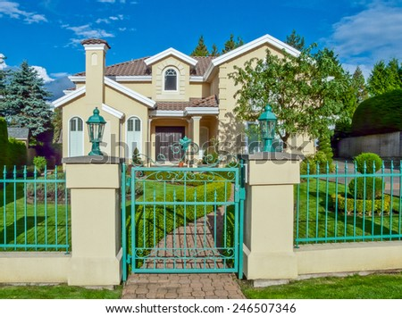 Custom built luxury house behind the gates with nicely trimmed front yard, lawn and long doorway in a residential neighborhood. Vancouver Canada. - stock photo