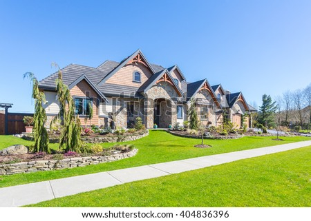 Custom built luxury house for sale with nicely trimmed and designed front yard, lawn in a residential neighborhood in Canada. - stock photo