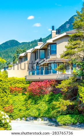 Custom built luxury house, town house with nicely trimmed front yard, lawn  in a residential neighborhood. Vancouver. Canada. Vertical. - stock photo