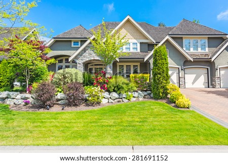 Custom built luxury house with nicely trimmed and designed front yard, lawn in a residential neighborhood in Canada. - stock photo
