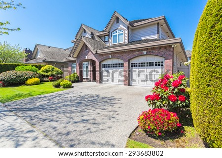 Custom built luxury house with nicely trimmed and designed front yard, lawn in a residential neighborhood in Canada.