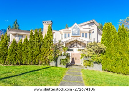 Custom built luxury house with nicely trimmed and landscaped front yard in a residential neighborhood. Vancouver Canada.  - stock photo