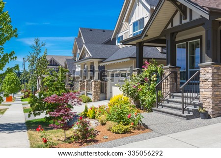 Custom built luxury house with nicely trimmed and landscaped front yard lawn and driveway to garage in a residential neighbourhood. Vancouver Canada. - stock photo