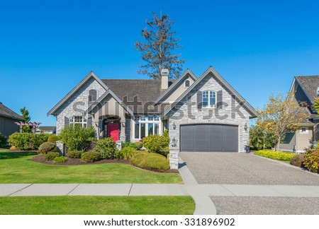 Custom built luxury house with nicely trimmed front yard, lawn and long doorway and driveway in a residential neighborhood. Vancouver Canada.