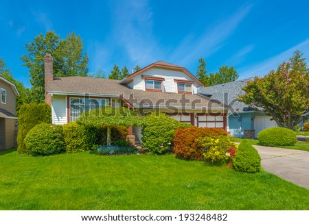 Custom built luxury house with nicely trimmed front yard, lawn and long driveway  to garage in residential neighborhood. Vancouver Canada.