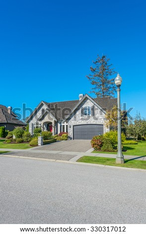 Custom built luxury house with nicely trimmed front yard, lawn and long driveway to garage in a residential neighborhood. Vancouver Canada. Vertical.