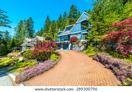 Custom built luxury house with nicely trimmed front yard, lawn and paved driveway to garage in a residential neighborhood. Vancouver Canada. - stock photo