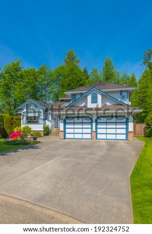 Custom built luxury house with nicely trimmed front yard, lawn and wide driveway to the double doors garage in a residential neighborhood. Vancouver Canada. Vertical.