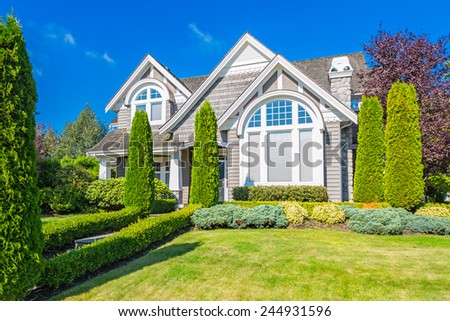 Custom built luxury house with nicely trimmed front yard, lawn in a residential neighborhood. Vancouver Canada. - stock photo