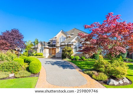 Custom built luxury house with nicely trimmed front yard, lawn in a residential neighborhood. Vancouver Canada.