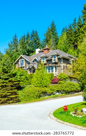Custom built luxury house with nicely trimmed front yard, lawn  in a residential neighborhood. Vancouver. Canada. Vertical. - stock photo