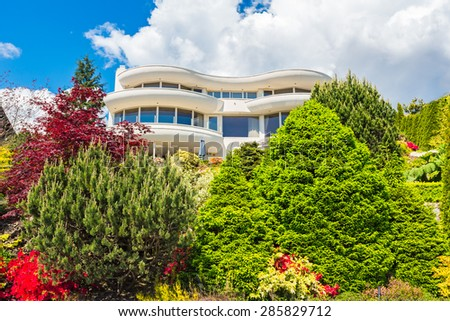 Custom built luxury modern house with nicely trimmed and landscaped front yard lawn  in a residential neighborhood.  - stock photo