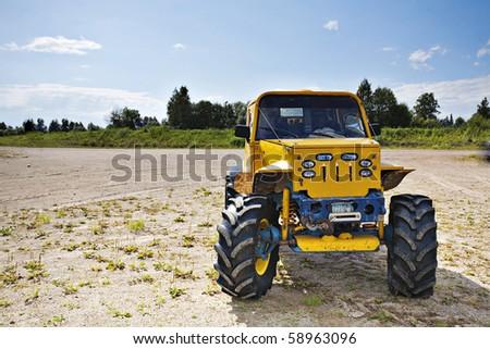 Custom built monster truck on edge of slope dangerously standing - stock photo