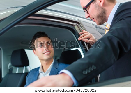 Customer buying new car in auto dealership