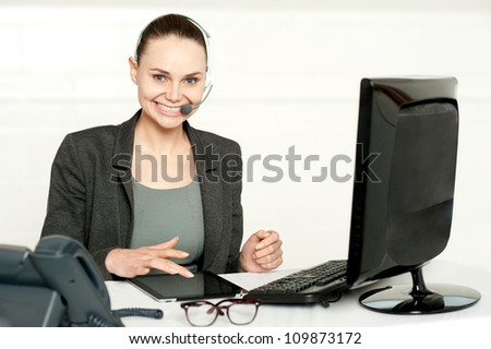 Customer care executive using tablet pc wearing headsets and looking at camera - stock photo