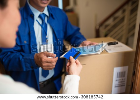 Customer giving credit card to the delivery man to pay for the order, selective focus - stock photo