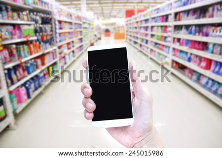 customer hand hold smartphone in supermarket , shopping online ,hand holding mobile smart phone on Supermarket blur background, retail business concept , rollback, internet - stock photo