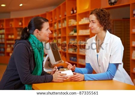 Customer having a discrete talk with pharmacist in pharmacy - stock photo