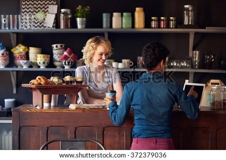 Customer In Coffee Shop Ordering Using Digital Tablet - stock photo