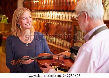 Customer Leaving Violin For Repair In Shop - stock photo