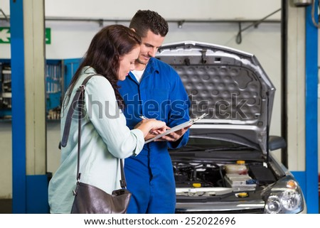 Customer listening to his mechanic at the repair garage
