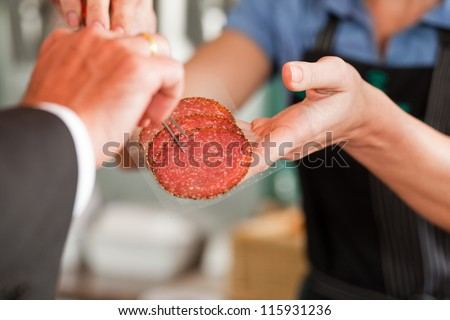 Customer looking at fresh meat steaks presented by butcher
