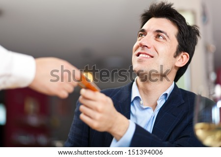 Customer paying bill at the restaurant with his credit card - stock photo