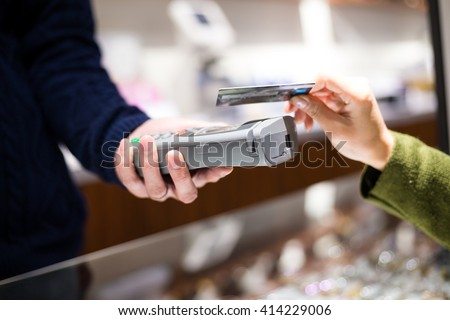 Customer paying credit card with NFC technology - stock photo