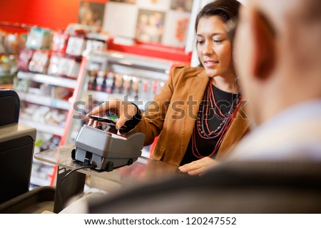 Customer paying for purchase with mobile phone - stock photo