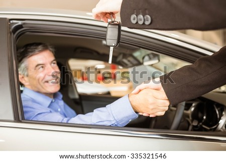 Customer receiving car keys while shaking hand in a garage