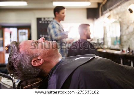 Customer Reclining In Barber's Chair Ready For Shave - stock photo