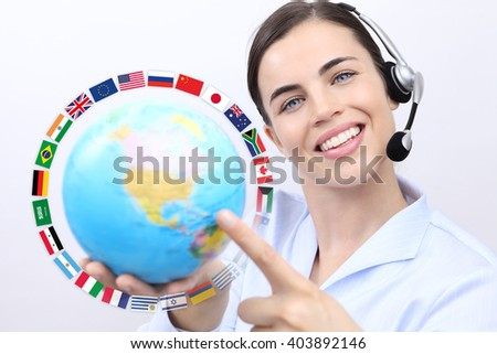 Customer service operator woman with headset smiling, holding globe, international flags, contact us concept - stock photo