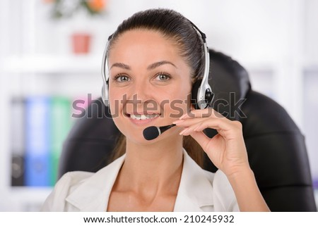Customer service representative at work. Confident middle-aged woman in headphones sitting at her working place and smiling - stock photo