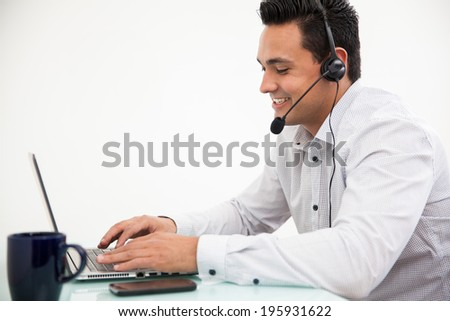 Customer service representative taking a call from a customer and smiling - stock photo